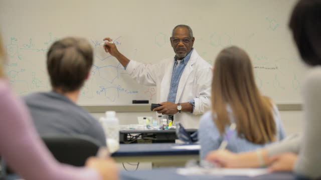 vidéos et rushes de locked-on shot of professor in college chemistry class with students - professor
