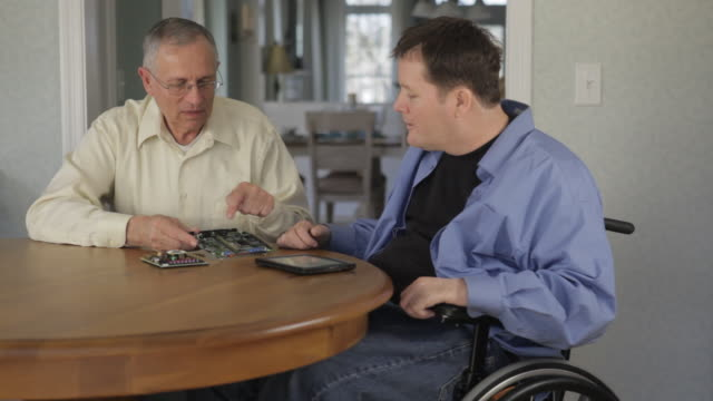 locked-on shot of two engineers one with quadriplegia discussing circuit board designs and putting data on tablet - persone con disabilità video stock e b–roll