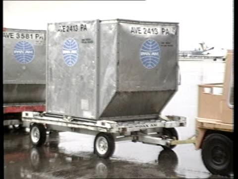 Terrorist bomb suspected ITN LIB ENGLAND London LAP Pan Am baggage vehicle towards with containers AV Pan Am symbol on tail plane MS Container on...