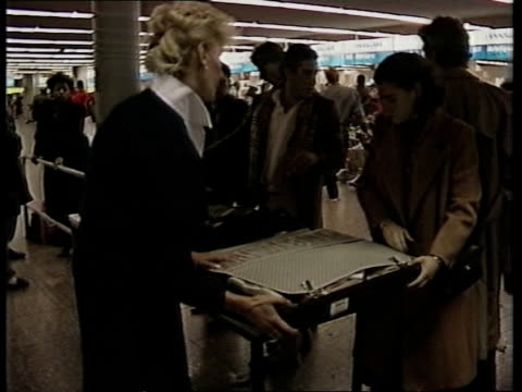 US reaction ITN LIB Female security official checking woman traveller's suitcase GV Row of checkin desks woman pushing luggage trolley along RL in...