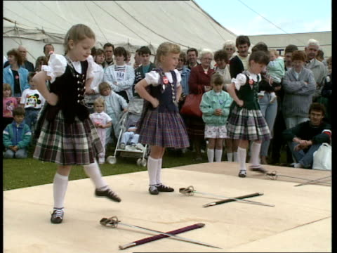 party thrown to thank residents for their support ext bags of presents handed out to children / three young girls in traditional costumes dance... - galloway scotland stock videos & royalty-free footage