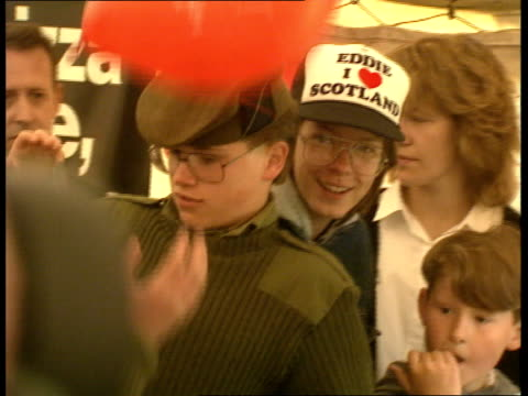 lockerbie party; scotland: lockerbie: bv young man throws pastry ? into crowd in tent boy eating piece of pizza zoom in cms youth in army uniform and... - eddie large stock videos & royalty-free footage