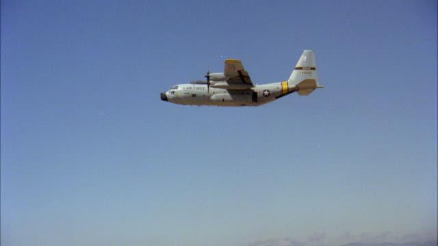 AIR TO AIR Lockheed C-130 Hercules flying against blue sky, parachutist jumping