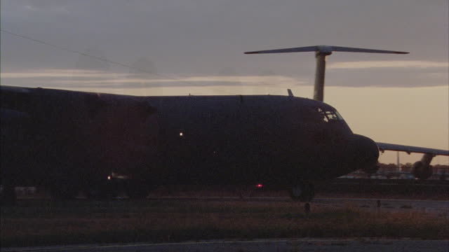 cu, lockheed c-130 hercules taxiing on runway at sunset, stewart international airport, new windsor, new york, usa - grobkörnig stock-videos und b-roll-filmmaterial
