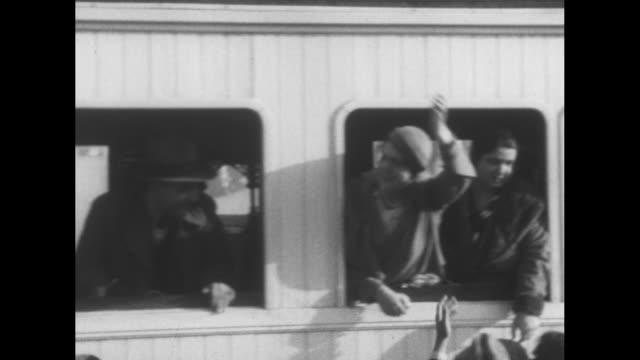 vidéos et rushes de locomotive and train station with people gathered around it / a diverse group of people and a woman on the train with a handkerchief / toddlers with... - locomotive