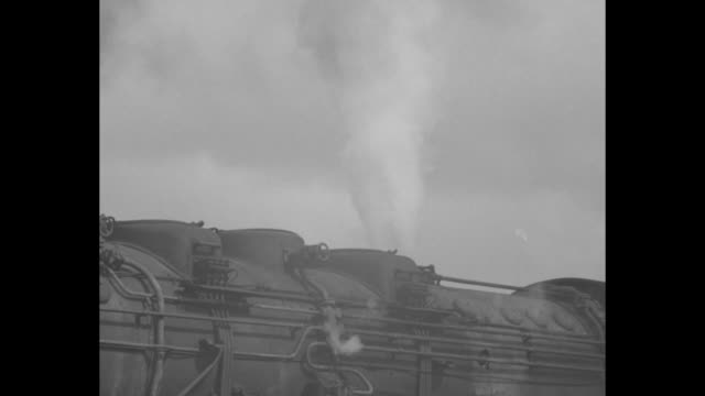 stockvideo's en b-roll-footage met a locomotive releases a plume of smoke and drumstickshaped signals for roadway / a ford automobile with v8 insignia drives on the autobahn - locomotief