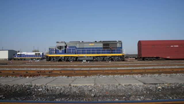 locomotive shunts at fengtaixi railway shunting yard of beijing - 操車場点の映像素材/bロール