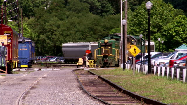 XWS Locomotive train reversing on railroad tracks few unidentifiable pedestrians vehicles crossing tracks Carbon County PA train yard