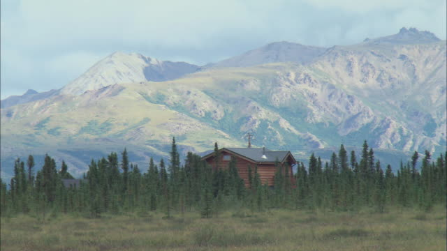 WS A log cabin with a mountain range behind / Alaska, United States