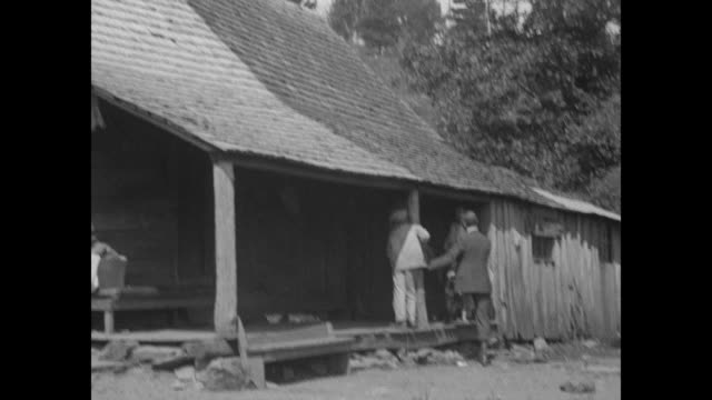 ls log cabin with horse tied to post on wooded mountainside homestead / mspan right cabin men working on the underside of porch roof / ms children... - mountain pose stock videos and b-roll footage