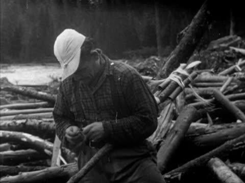 Log drivers w/ poles trying to loosen logs jam MS Log driver lighting bound sticks of dynamite pushing under water log jam WS Logs exploding moving...