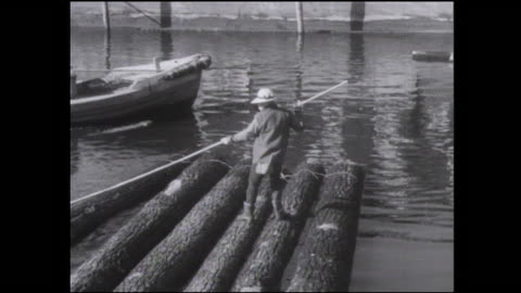 a logger makes a log raft and then uses a pole as he floats the raft under a bridge. - log stock videos & royalty-free footage