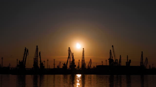 logistics and transportation of container cargo ship and cargo with working crane bridge in shipyard at sunset - jetty stock videos & royalty-free footage