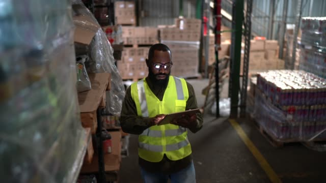 logistics employee walking and using digital tablet at warehouse - packaging stock videos & royalty-free footage