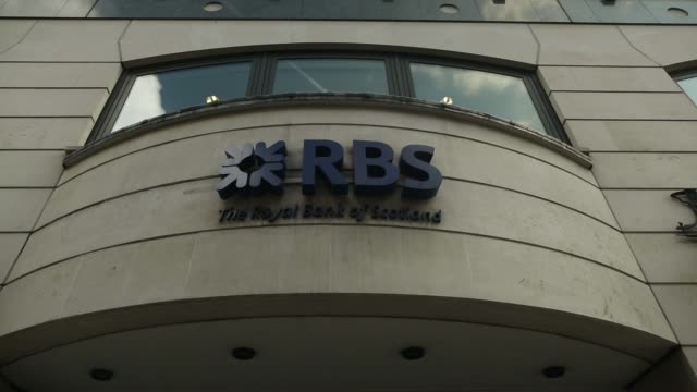 A logo hangs on display outside a branch of Royal Bank of Scotland Group Plc in London UK on Wednesday July 31 2013 PAN RL RBS Logo hanging on...