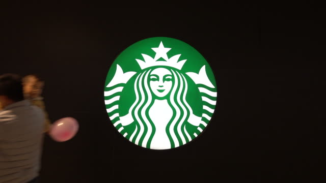 logo lightbox on the wall of a newly opened starbucks coffee shop. in november, starbucks predicted that the same store sales in chinese market will... - catena di negozi video stock e b–roll