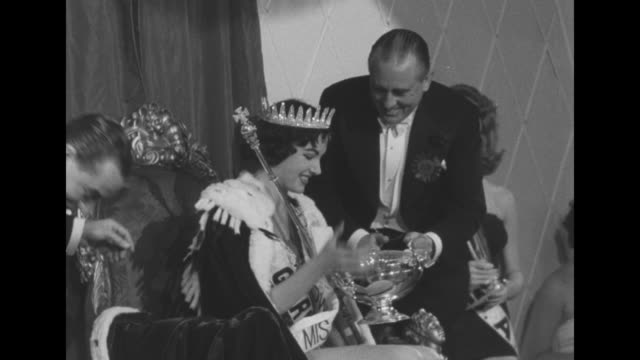 logo miss world 1956 / judge gives petra schurmann a silver trophy / cameramen / petra poses with other contestants / cu petra in crown with trophy / - miss world pageant stock videos & royalty-free footage