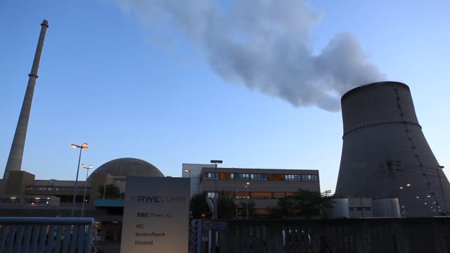 vídeos y material grabado en eventos de stock de logo sits on display as a cooling tower emits vapor beside buildings housing a nuclear power plant operated by rwe ag, in emsland, germany, on... - nuclear energy