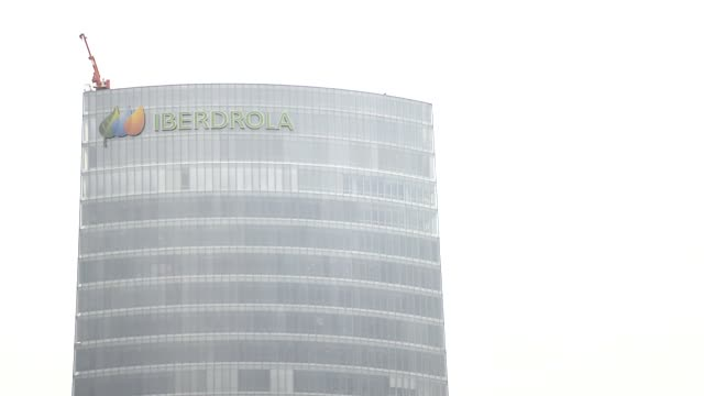 vídeos de stock, filmes e b-roll de logo sits on display outside the headquarters of iberdrola sa in bilbao, spain, on tuesday, july 16 pedestrians pass the spider maman steel sculpture... - high street