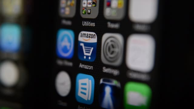 logos and the app icon of Amazon com are displayed on monitors smartphones and tablets in a dark studio space in Tiskilwa Illinois Close up shots pan...