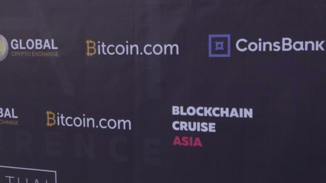 Logos for Coinsbank Blockchain and Bitcoin on a display board during a Coinsbank Blockchain Cruise Asia conference event at Paradise Beach in Phuket...