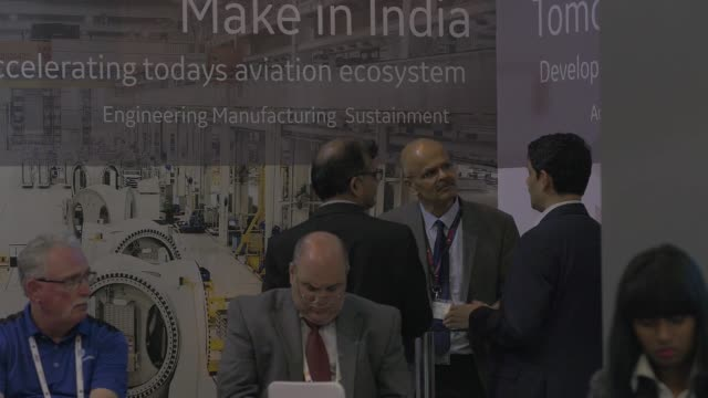 logos on display as attendees stand at the general electric co booth during the aero india air show at air force station yelahanka in bengaluru india... - general electric stock videos and b-roll footage