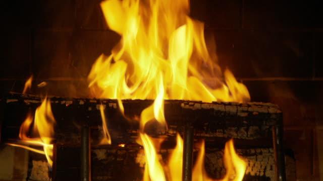 Logs burn in a fireplace.