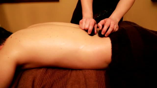 Loin lastone massage of a dark-haired charming man