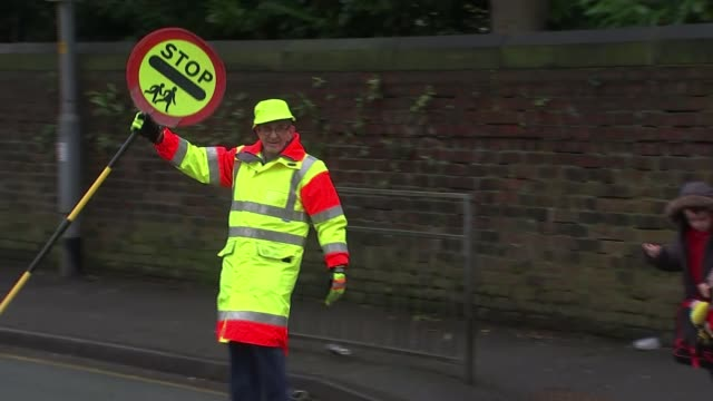 Lollipop man allowed to high five children after local outcry ENGLAND Greater Manchester Stockport EXT Various of Colin Spencer highfiving children...