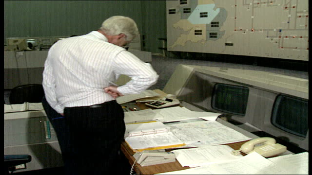 London 0240 GVs National Grid Control Room as man looks at huge SE1 map of electricity grid BV staff at consoles looking at printouts MS football on...