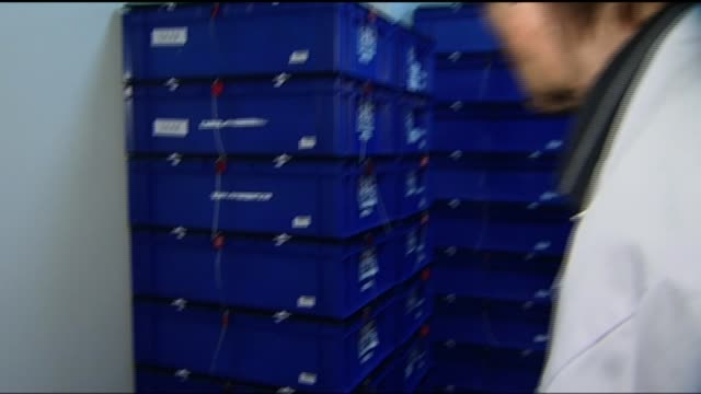 doping retests reveal 23 drugs cheats t16071332 / 1672013 switzerland lausanne int scientist into refrigerated room containing boxes of samples taken... - tag 7 stock-videos und b-roll-filmmaterial