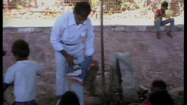 vídeos de stock e filmes b-roll de dow chemical controversy india threaten boycott 6121984 / as061284012 india bhopal man handing out clothing to children woman and children along road... - the dow chemical company