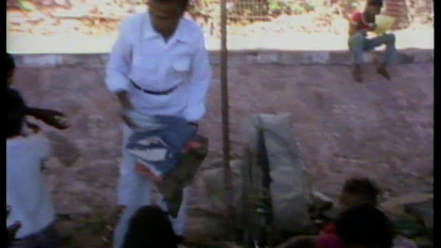 Indian government protests against key Olympic sponsor 6121984 / AS061284012 INDIA Bhopal Man handing out clothing to children Woman and children...
