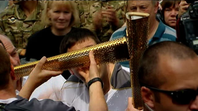 injured paratrooper carries olympic torch england yorkshire doncaster ext police escort for london 2012 olympic torch relay ben parkinson sitting... - 継父点の映像素材/bロール