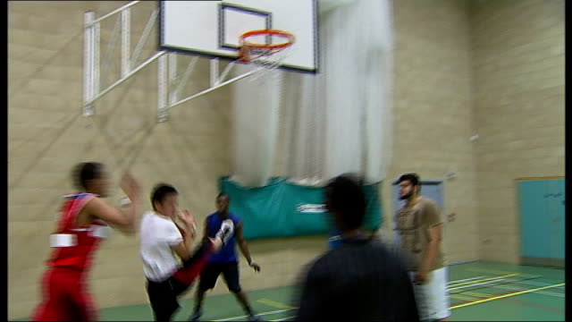 london 2012 olympic games: legacy debate; ilford: frenford sports club: young men playing basketball in gym vox pops young men playing baksetball... - ilford stock videos & royalty-free footage
