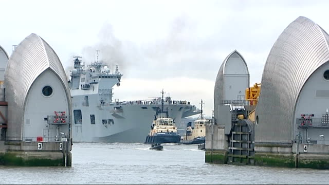 vidéos et rushes de military security exercises begin england south east london thames barrier ocean guided by tugs as passing through thames flood barrier - fleuve tamise