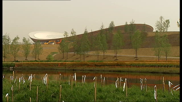 stockvideo's en b-roll-footage met olympic park to provide lasting legacy gv newly planted olympic park with aquatic centre in b/g coot swimming on river - koet