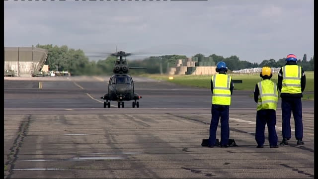 olympic security preparations at raf northolt england middlesex raf northolt ext military helicopter landing on runway / men putting chocks behind... - bremskeil stock-videos und b-roll-filmmaterial