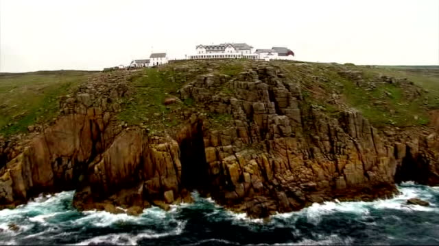 olympic torch arrives on british soil air view of coastline and rocks at land's end - olympic torch stock videos & royalty-free footage