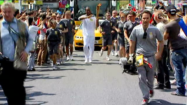 Olympic Torch relay Didier Drogba carries Torch ENGLAND Wiltshire Swindon EXT Didier Drogba carrying 2012 Olympic torch past cheering crowds Reporter...