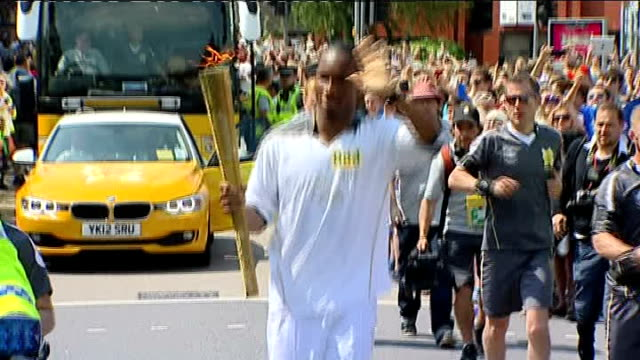 Olympic Torch relay Didier Drogba carries Torch ENGLAND Wiltshire Swindon EXT Didier Drogba along waving and holding Olympic flame in torch relay...