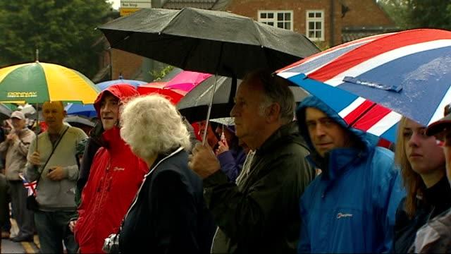 vidéos et rushes de london 2012 olympic games: olympic torch relay in stevenage; england: hertfordshire: stevenage: ext / raining various of people lining street vox pops - vox populi