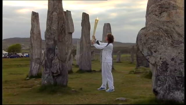 london 2012 olympic games: olympic torch relay reaches stornoway and balmoral; scotland: stornoway & balmoral. ext gv woman playing bagpipes at... - flaming torch stock videos & royalty-free footage