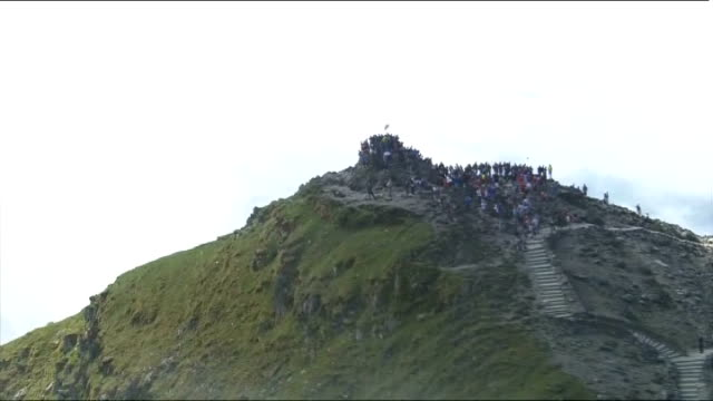 london 2012 olympic games: olympic torch relay: sir chris bonington takes flame to top of mount snowdon; air view / aerial people crowded onto the... - flaming torch stock videos & royalty-free footage