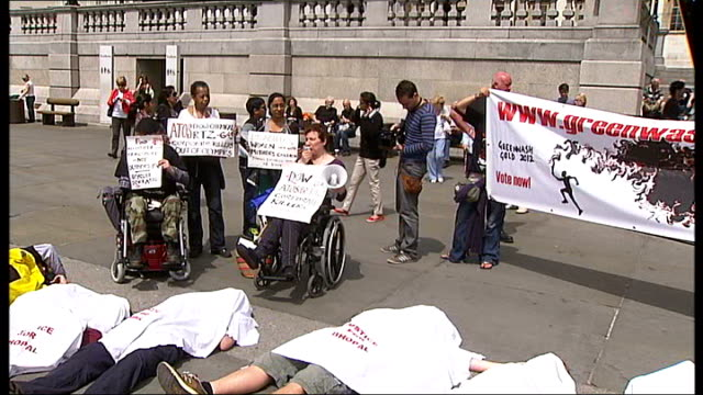 vídeos de stock e filmes b-roll de one month to go olympic rings suspended from tower bridge trafalgar square ext protesters lying on floor and using mega phone to protest against dow... - the dow chemical company