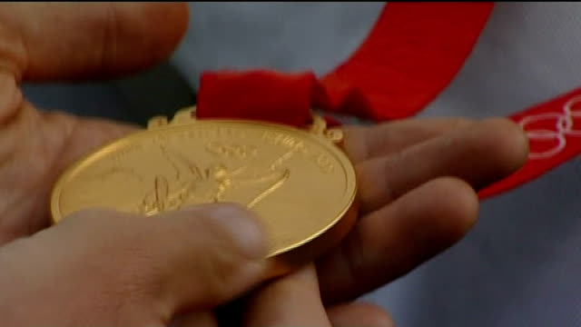 sir chris hoy to lead british athletes / dress rehearsal for opening ceremony lib heathrow int close shot olympic gold medal rebecca adlington and... - olympic medal stock videos & royalty-free footage