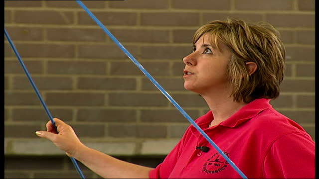 sutton school of gymnastics to close borrutzu looking on as girl dismounts from uneven bars - uneven stock videos & royalty-free footage