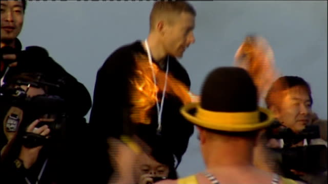 torch arriving in lands end england cornwall land's end ext jonathan edwards interview sot / general views of clown with fire juggling sticks along... - lands end cornwall stock videos and b-roll footage