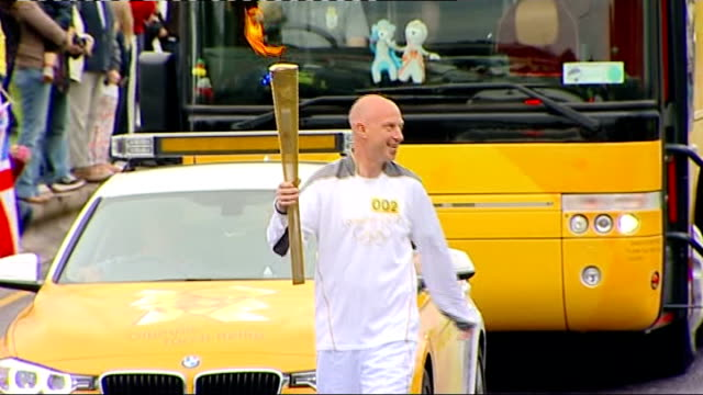 torch relay in devon england devon plymouth ext general views of various olympic torchbearers running and handing over torch including crowds... - olympic torch stock videos & royalty-free footage