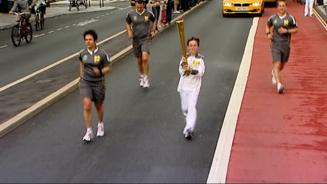 torch relay in devon more of torchbearers running and handing over torch including crowds cheering and running along / general view of handover to... - olympic torch stock videos & royalty-free footage